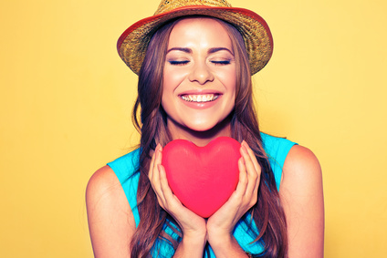 Young woman portrait with closed eyes holding red Heart. Love symbol.