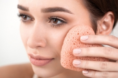beautiful woman make a facial treatment with a  sponge