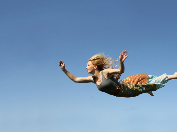 A young woman is falling as if flying through the air in front of a blue sky background.