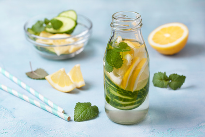 Summer drink with cucumber, lemon, mint in a glass bottle on a blue background