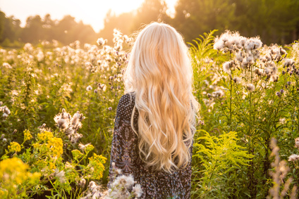 Long haired blond woman turned back on sunset meadov - outdoor image