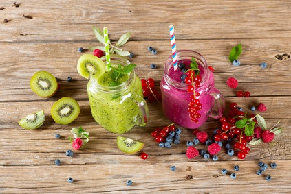 Smoothie and milkshake with variety fresh fruits and berries (kiwi, red currant, blueberry, raspberry) in a mason jar on a old wooden background.